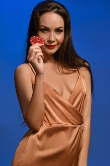 Young brunette girl in silk golden dress she smiling showing two red chips posing against blue wall