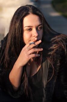 옆을 바라보며 담배를 피우면서 벽에 앉아 있는 어린 갈색 머리 소녀
