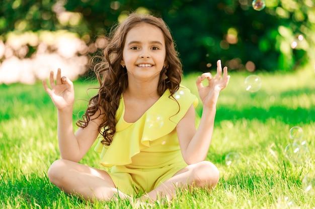 公園の芝生の上に座っている若いブルネットの少女。高品質の写真