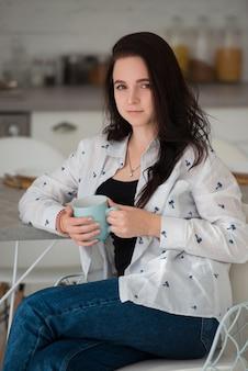Молодая брюнетка студентка сидит на стуле утром на кухне с чашкой кофе