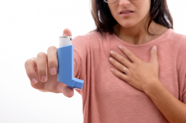 Young brunette girl suffers from asthma inhaling showing an inhaler isolated.