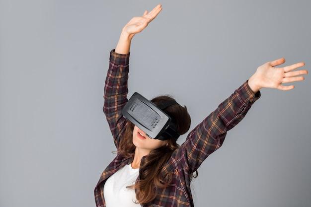 회색 배경 스튜디오에서 가상 현실 헬멧을 테스트하는 어린 갈색 머리 소녀