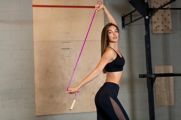 若いブルネットの少女はジムで縄跳びで訓練します