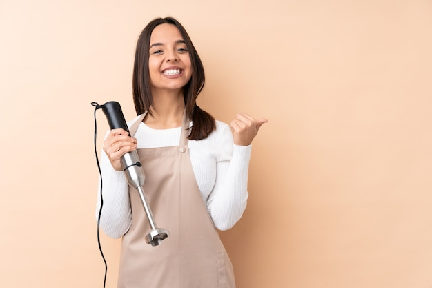 Young brunette girl using hand blender over isolated background pointing to the side to present a product