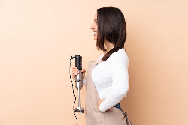 측면 위치에서 격리 된 배경 위에 핸드 블렌더를 사용하는 젊은 갈색 머리 소녀