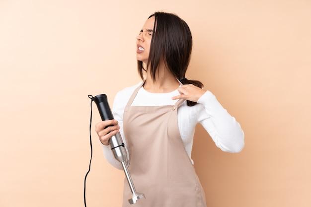 Молодая брюнетка девушка с помощью ручного блендера на изолированном фоне с усталым и больным выражением лица