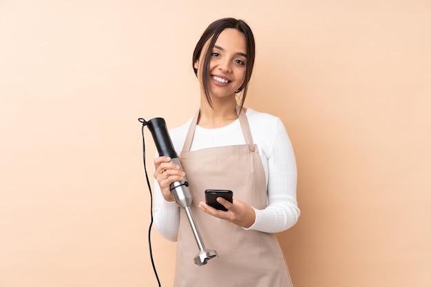 모바일로 메시지를 보내는 격리 된 벽에 핸드 블렌더를 사용하는 젊은 갈색 머리 소녀