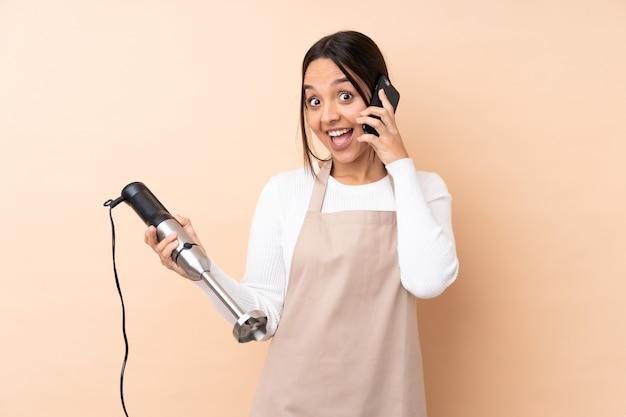 누군가와 휴대 전화로 대화를 유지하는 동안 핸드 블렌더를 사용하는 젊은 갈색 머리 소녀
