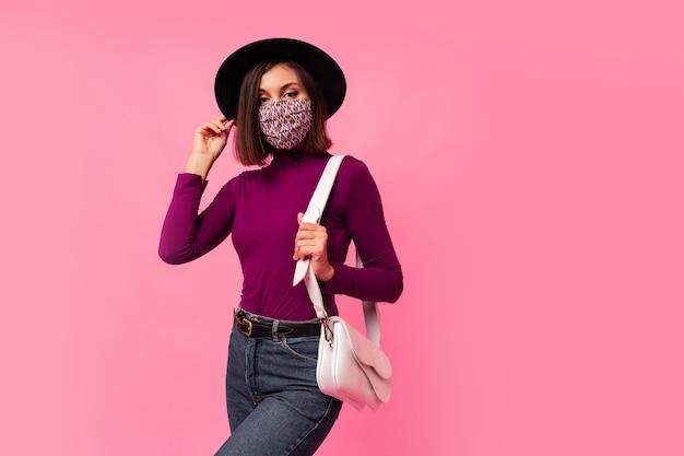 Молодая брюнетка девушка в респираторной маске против коронавируса