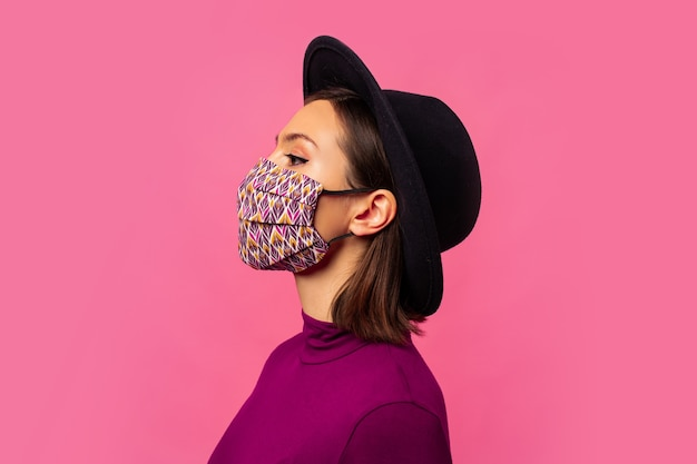 Young brunette girl wearing respiratory face mask against coronavirus