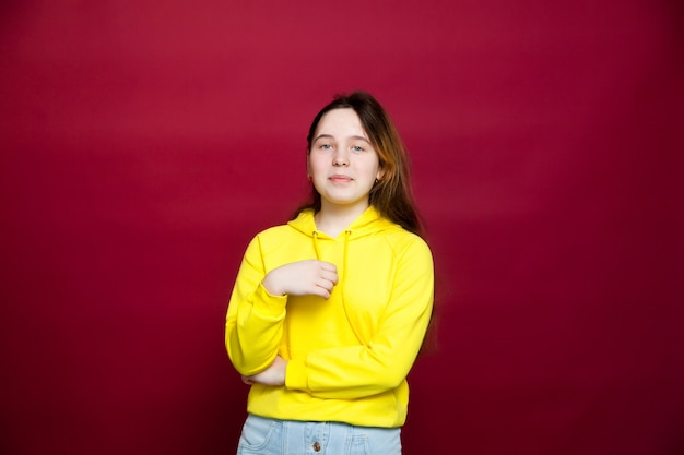 빨간 벽에 고립 된 서 세련된 노란색 까마귀를 입고 젊은 갈색 머리 소녀