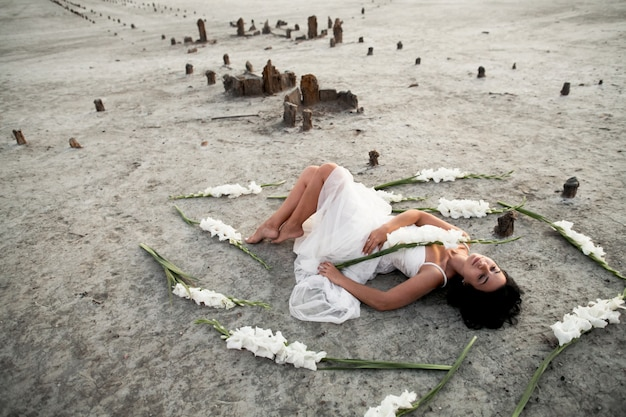 Young brunette girl in white dress with closed eyes is lying on the seacoast surrounded with white gladioluses