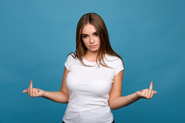 Young brunette girl in white t-shirt showing middle finger