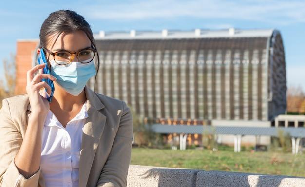 彼女のオフィスの外の公園のベンチで作業しているフェイスマスクを持つ若いブルネットの少女。彼女の携帯電話で話している。ビジネスコンセプト、テクノロジー、在宅勤務。コロナウイルスパンデミック。