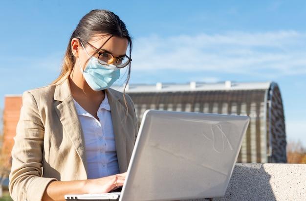 彼女のオフィスの外の公園のベンチで作業しているフェイスマスクを持つ若いブルネットの少女。彼女のラップトップでの作業。ビジネスコンセプト、テクノロジー、在宅勤務。コロナウイルスパンデミック。