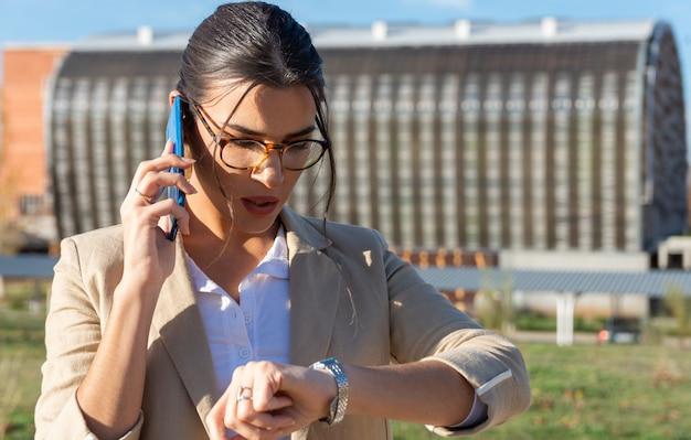 그녀의 사무실에서 작동하는 얼굴 마스크와 젊은 갈색 머리 소녀. 그녀의 휴대 전화를 사용 하 고 그녀의 시계를보고. 비즈니스, 기술 및 재택 근무의 개념.