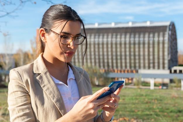 그녀의 사무실에서 일하는 얼굴 마스크와 젊은 갈색 머리 소녀. 그녀의 휴대 전화를 사용합니다. 비즈니스 개념, 기술 및 재택 근무.