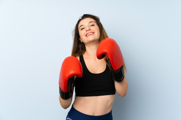 Young brunette girl with boxing gloves over isolated background