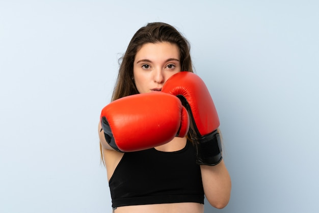 Young brunette girl with boxing gloves over isolated wall