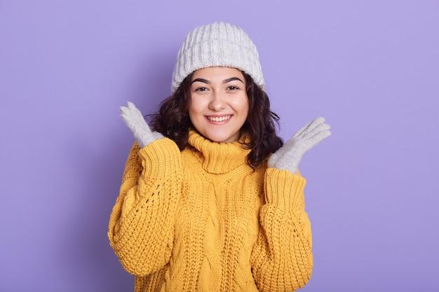 Giovane ragazza bruna con sorriso carino diffondendo le palme da parte