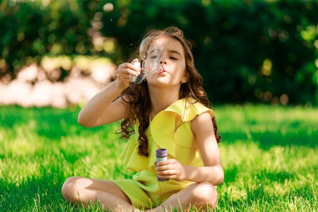 Молодая брюнетка с темными волосами сидит на траве в парке и пускает мыльные пузыри. фото высокого качества