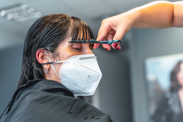 彼女の前髪を切るヘアーサロンでフェイスマスクを持つ若いブルネットの少女。 covid-19パンデミックにおける美容院のセキュリティ対策を再開。新しい正常、コロナウイルス、社会的距離
