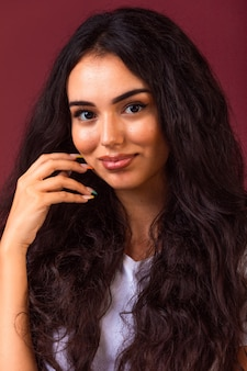 Giovane ragazza bruna con i capelli lunghi e ricci che promuovono lo stile di trucco autunnale.