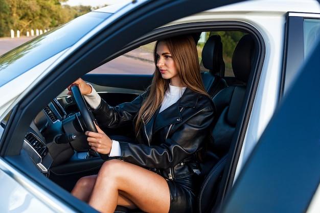 가죽 블랙 재킷에 긴 머리를 한 젊은 갈색 머리 소녀와 비싼 차를 몰고 아름다운 다리를 가진 치마. 차를 운전하는 어린 소녀