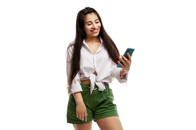 A young brunette girl with long hair in a white shirt and green shorts looks at a smartphone. online chat. isolated on a white background.