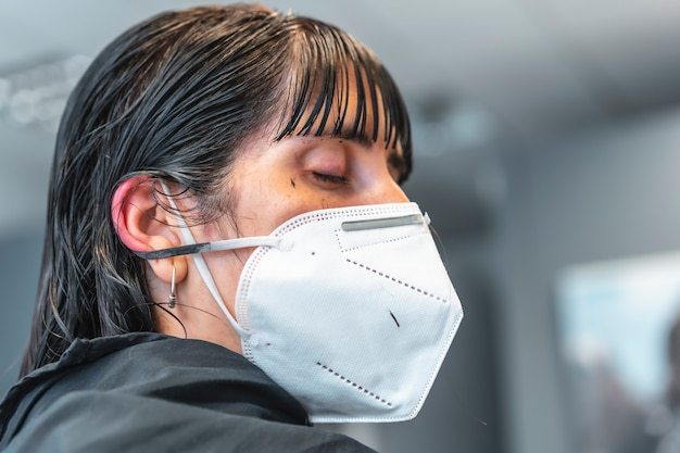 Young brunette girl with mask in a hair salon. reopening with security measures for hairdressers in the covid-19 pandemic. new normal, coronavirus, social distance