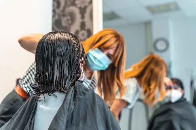 Young brunette girl with mask in a hairdresser cutting her hair reflected in the mirror. safety measures for hairdressers in the covid-19 pandemic. new normal, coronavirus, social distance