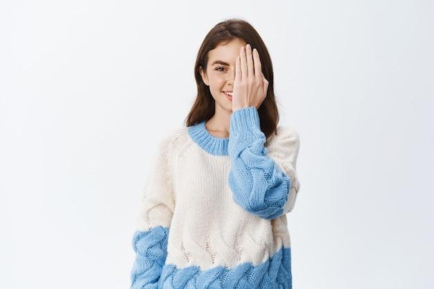 自然な顔と光の若いブルネットの女の子は、白い壁に立って、効果の前に前に表示するために手のひらの手で顔の半分を覆っています