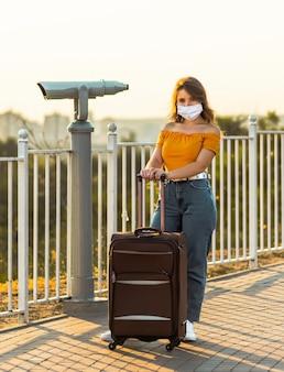 サージカルマスクを持つ若いブルネットの少女は、公園の双眼鏡の近くに彼女のスーツケースでポーズをとっています。