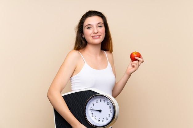 Young brunette girl  with weighing machine and with an apple over isolated wall
