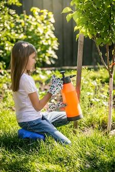 肥料スプレーで庭で働く若いブルネットの少女