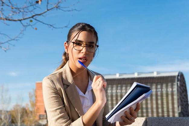 彼女のオフィスの外の公園のベンチで働いている若いブルネットの少女。彼女の議題に書く。ビジネスコンセプト、テクノロジー、在宅勤務。