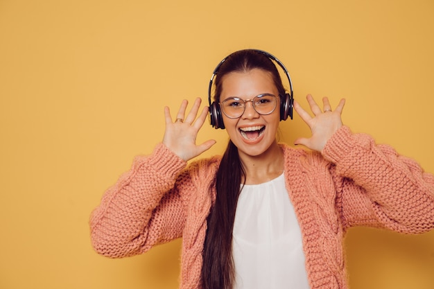 Young brunette in glasses and headphones dressed in pink sweater white blouse laughing with open mouth, raised her hands up, over yellow background. positive and young.