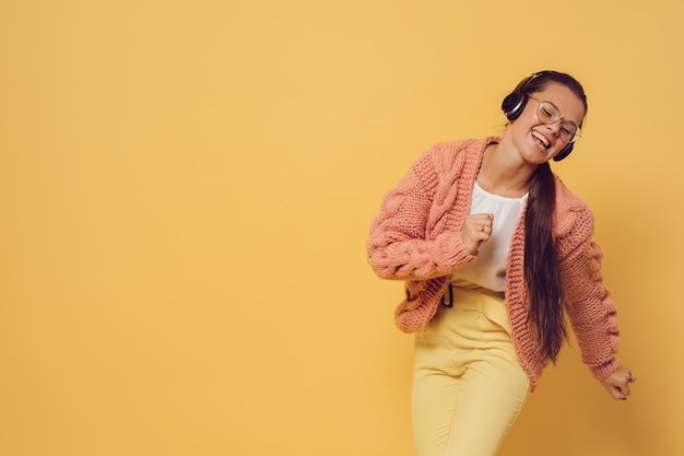 Young brunette in glasses and headphones dressed in pink sweater white blouse and yellow pants singing and dancing satisfied by her lifestyle, over yellow background. positive and young. party time.