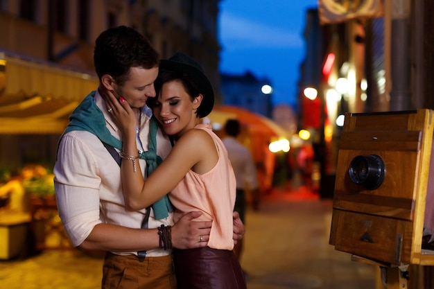 Young brunette and handsome guy hugging on the street at night