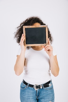 Young brunette hiding face behind blackboard