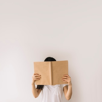 Young brunette hiding face behind book
