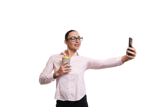 腕の長さで携帯電話を保持しているホットドリンクとリサイクル段ボールクラフトマグカップとピンクのシャツの若いブルネット。