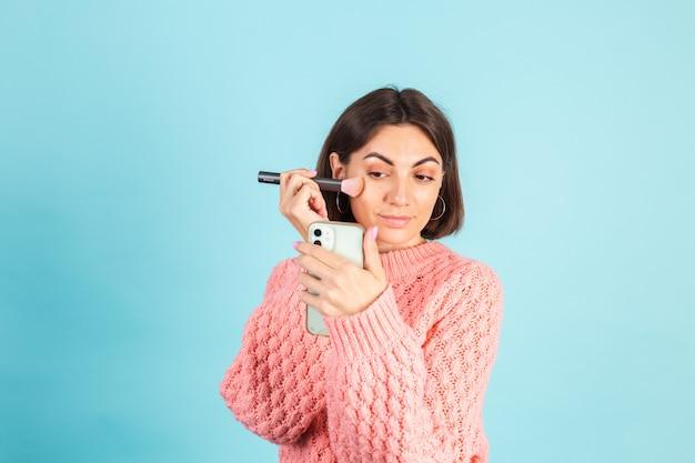 파란색 벽에 고립 된 분홍색 스웨터에 젊은 갈색 머리