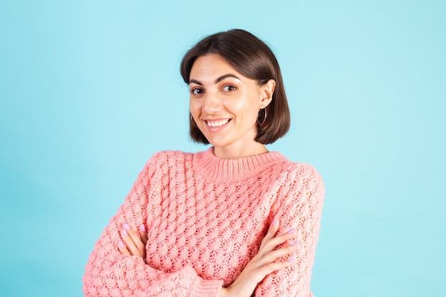 青い壁に分離されたピンクのセーターの若いブルネット