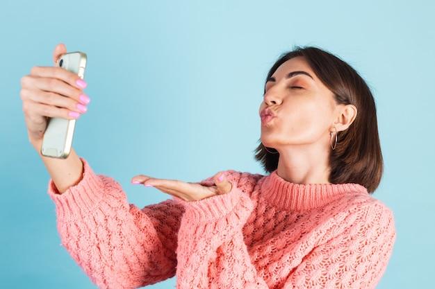 Молодая брюнетка в розовом свитере изолирована на синей стене