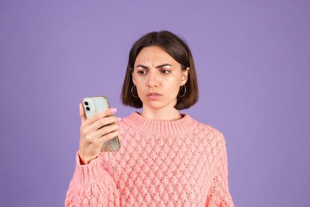 Молодая брюнетка в розовом свитере изолирована на фиолетовой стене