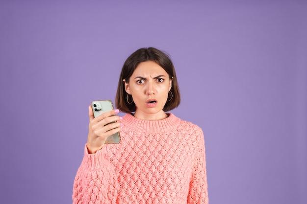 보라색 벽에 고립 된 분홍색 스웨터에 젊은 갈색 머리