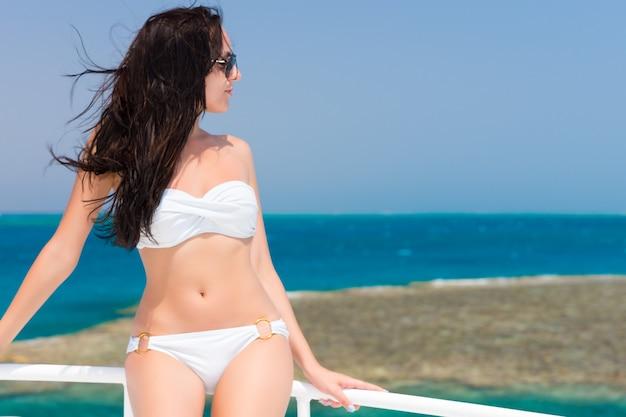 晴れた夏の日にヨットの上に立っている水着の若いブルネット、そよ風の発達する髪、背景の美しいターコイズブルーの海