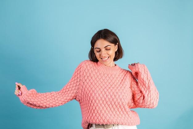 Молодая брюнетка в теплом розовом свитере изолирована на синей стене