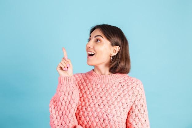 파란색 벽에 고립 된 따뜻한 분홍색 스웨터에 젊은 갈색 머리